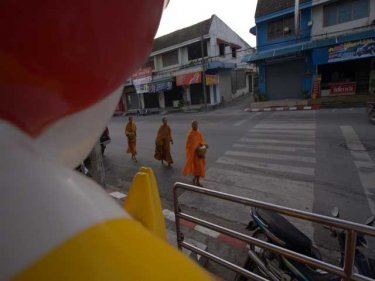 Cultures meet as monks are waied at a burger joint in Phuket City