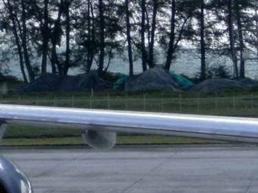 Phuket airport plane crash wreckage under tarpaulins by the sea