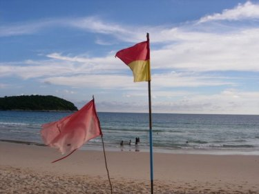 Flags fly at Naiharn beach, one of Phuket's popular swimming destinations
