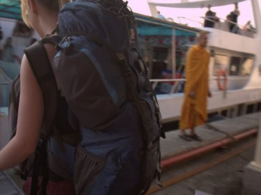 A backpacker boards a large ferry for Phi Phi at Rassada Port on Phuket