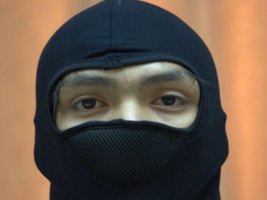 Masked for his protection, a youth appears at Phuket City police station