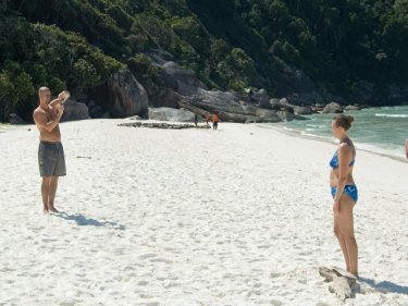 Tourists on one end of a Similans beach, prostrate boatpeople at the other