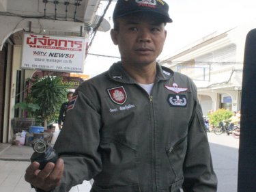 A Phuket policeman shows off the grenade left outside a yellow tv office