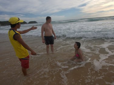 A lifeguard struggles to get swimmers to leave the water at Karon after a drowning