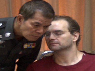 Ronald Fanelli whispers to a policeman at Phuket City police station