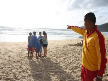 A lifeguard points out to sea at Karon during yesterday's search for a lost tourist