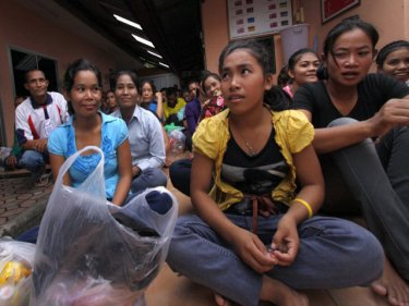 Cambodians wait at Phuket's Immigration HQ for the bus ride home
