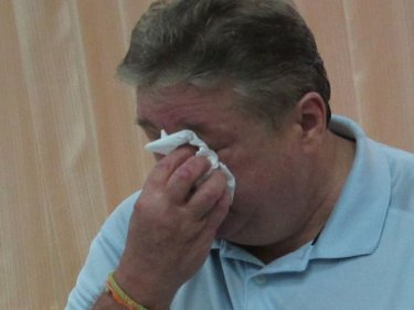 Roger A. Miller dabs his face as he tells the media on Phuket he's broke