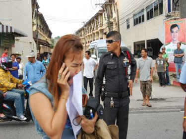 Khun Ji takes a call at the spot where her husband was killed today