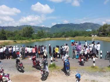 A crowd gathers at the spot where the Krabi man's car went under today