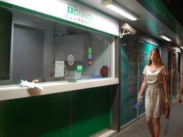 A tourist passes the currency booth in Phuket's Kata district  last night