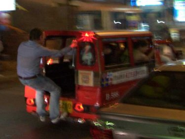 A New Year reveller swings from a tuk-tuk as a woman takes video