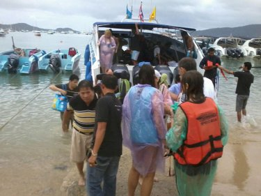 A speedboat drops rescued passengers ashore on Phuket late today