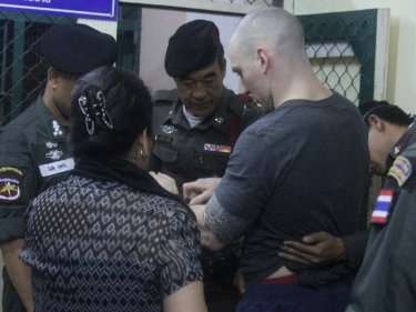 Lee Aldhouse surrenders his chunky watch outside a Phuket cell last night