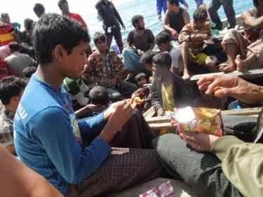 Children enjoy snacks off Phuket after 13 days at sea in an open boat