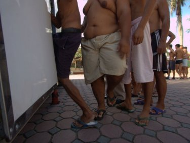 Male inmates queue for a health check inside Phuket Prison