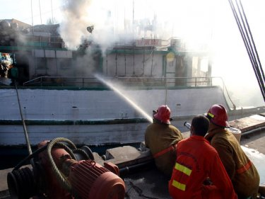 Firemen douse the blaze on the Indonesian fishing boat off Phuket
