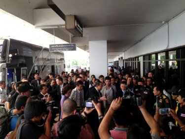 The media throng surrounds officials outside Phuket airport today