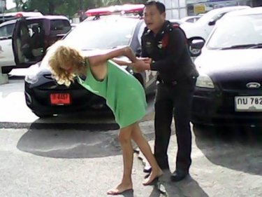 A Phuket officer restrains the Russian woman today