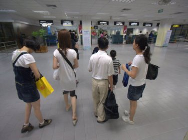 Passengers at Phuket airport prepare to pass through Immigration
