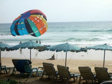 A parasail operator advertises effortlessly in the breeze on Karon beach