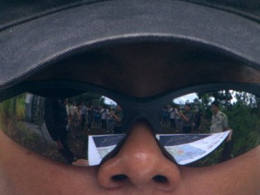 A map of the resort area is reflected in the sunglasses of an investigator