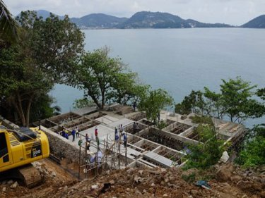 A crane is being used to lower equipment on a steep Phuket site
