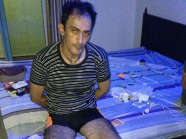 Safari Behzad, 44, in the Patong room where he was arrested early today