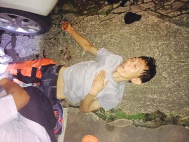 The shot Phuket bandit lying wounded near his getaway car last night