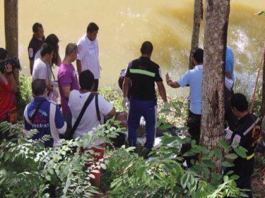 The man's body is fetched from the pond in Phuket City this afternoon