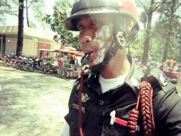 Like it or not, a Patong policeman celebrates Songkran