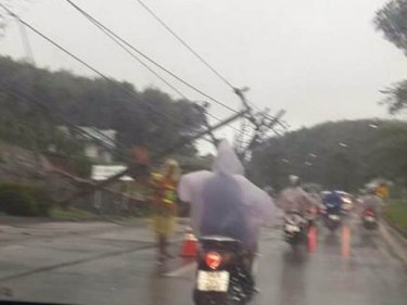 A wall and a power pole collapse during heavy rain in Phuket City today