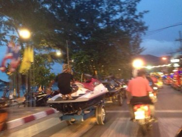 A string of jet-skis being towed by a motorcycle with sidecar in Patong